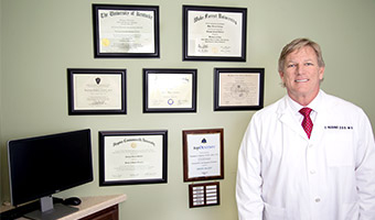 Male dental doctor standing in front of awards and honors.
