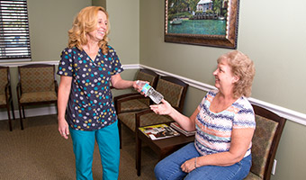 Dental assistant handing a new patient a bottle of water.