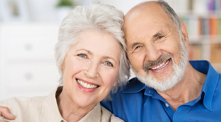 Elderly man and woman smiling with new teeth.