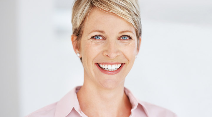 Woman smiling in the dentist office after receiving diagnosis.